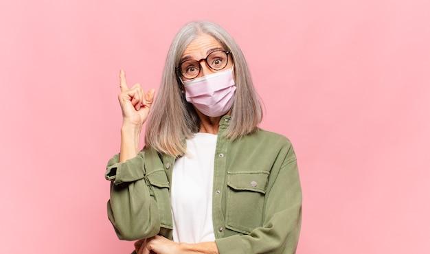 Donna di mezza età che si sente come un genio felice ed eccitato dopo aver realizzato un'idea, alzando allegramente il dito, eureka!