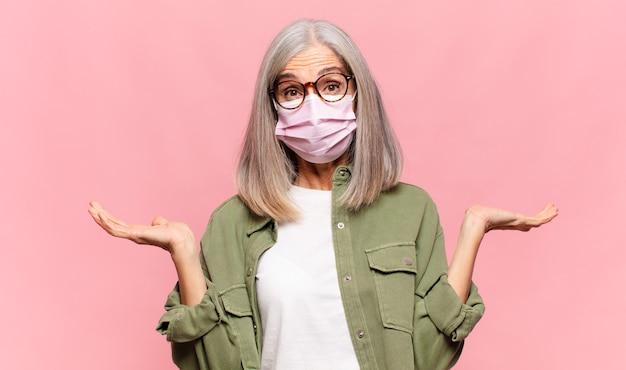 Donna di mezza età che si sente perplessa e confusa, dubita, appesantisce o sceglie diverse opzioni con un'espressione divertente