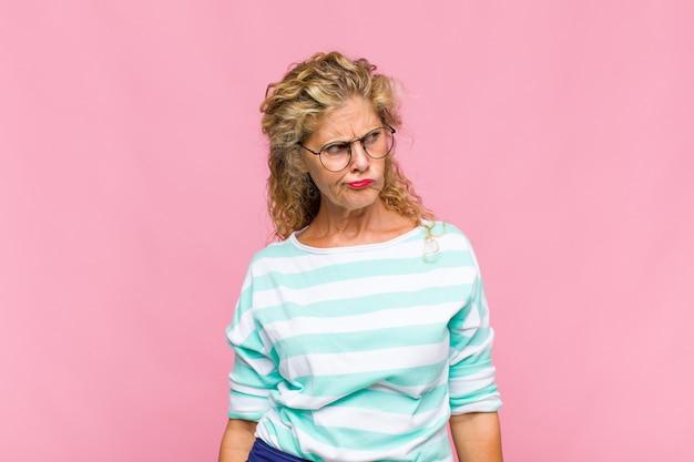 Donna di mezza età che si sente triste, turbata o arrabbiata e guarda di lato con un atteggiamento negativo, aggrottando la fronte in disaccordo