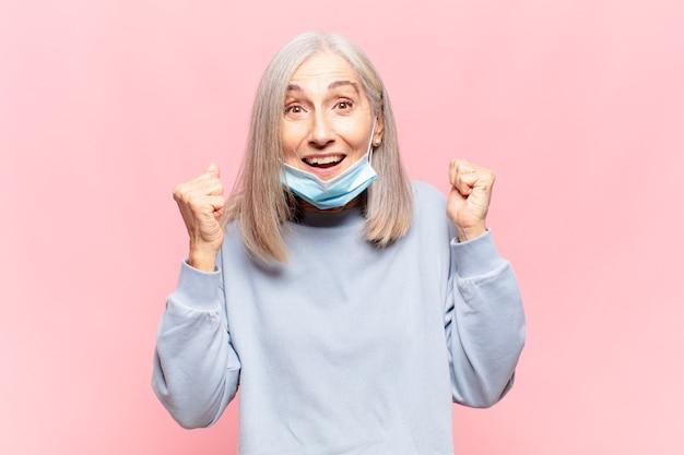 Donna di mezza età che si sente scioccata, eccitata e felice, ride e celebra il successo, dicendo wow!