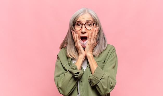 Donna di mezza età che si sente scioccata e spaventata, sembra terrorizzata con la bocca aperta e le mani sulle guance