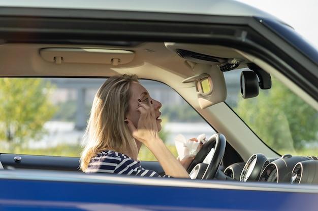 Donna di mezza età fissare il trucco guardando nello specchietto retrovisore guidare l'auto femmina conducente distrarre dalla strada