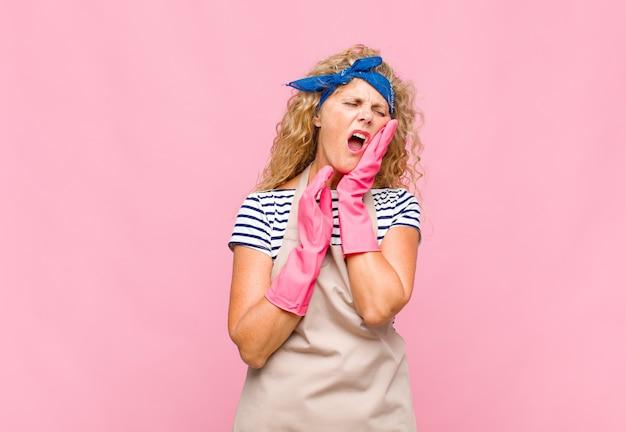 Donna di mezza età che tiene la guancia e soffre di mal di denti doloroso, sensazione di malessere, infelice e infelice, alla ricerca di un dentista