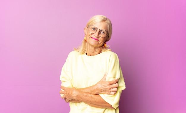 Donna di mezza età che ride felice con le braccia incrociate, con una posa rilassata, positiva e soddisfatta