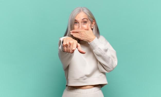 Donna di mezza età che ride di te, indica in avanti e ti prende in giro o ti prende in giro