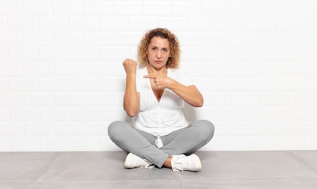 Una donna di mezza età che sembra impaziente e arrabbiata, indica l'orologio, chiede puntualità, vuole essere puntuale
