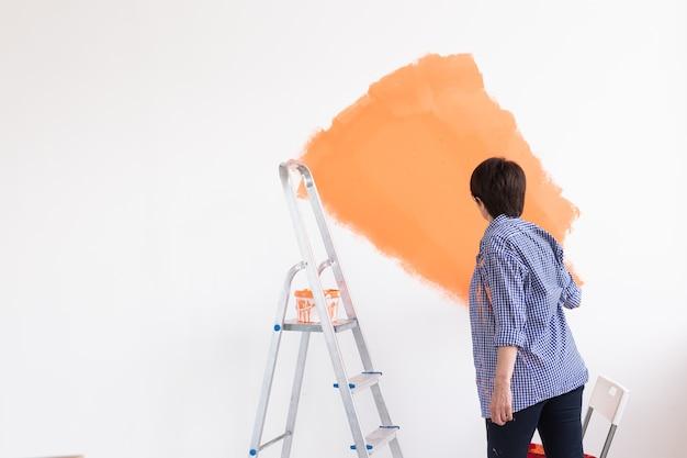 Donna di mezza età che dipinge le pareti della nuova casa. concetto di ristrutturazione, riparazione e ristrutturazione. copia