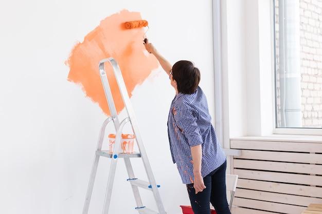 Donna di mezza età che dipinge le pareti della nuova casa. concetto di ristrutturazione, riparazione e ristrutturazione.