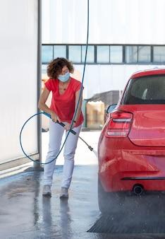 Donna di mezza età in maschera protettiva pulisce l'auto con acqua ad alta pressione