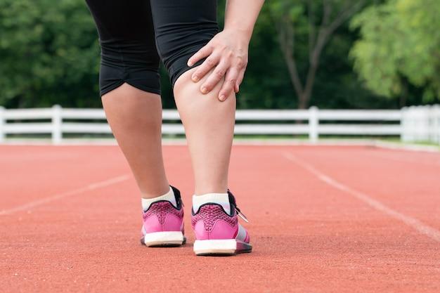 Dolore muscolare corridore donna di mezza età durante l'allenamento all'aperto