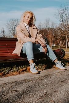 Donna di mezza età che si siede sulla panchina al parco cittadino di autunno