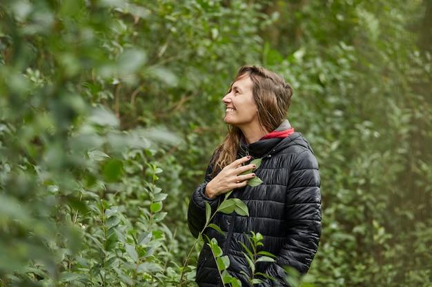 Donna di mezza età che sorride nella boscaglia mentre accarezza le foglie degli alberi in inverno. capelli biondi caucasici