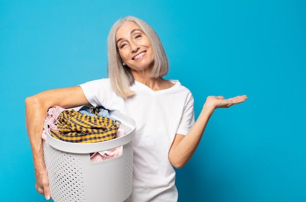 Donna di mezza età che sorride allegramente, sentendosi felice e mostrando un concetto nello spazio della copia con il palmo della mano