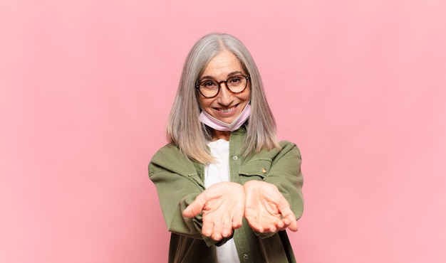Donna di mezza età che sorride felicemente con uno sguardo amichevole, fiducioso, positivo, offrendo e mostrando un oggetto o un concetto