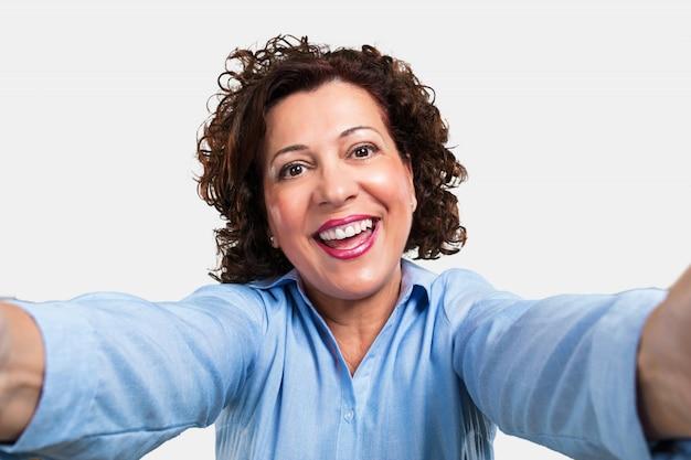 Donna di mezza età sorridente e felice, prendendo un selfie, tenendo la fotocamera