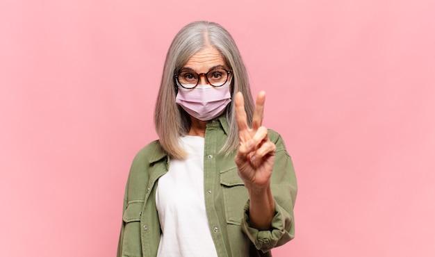 Donna di mezza età che sorride e sembra amichevole, mostrando il numero due o il secondo con la mano in avanti, il conto alla rovescia