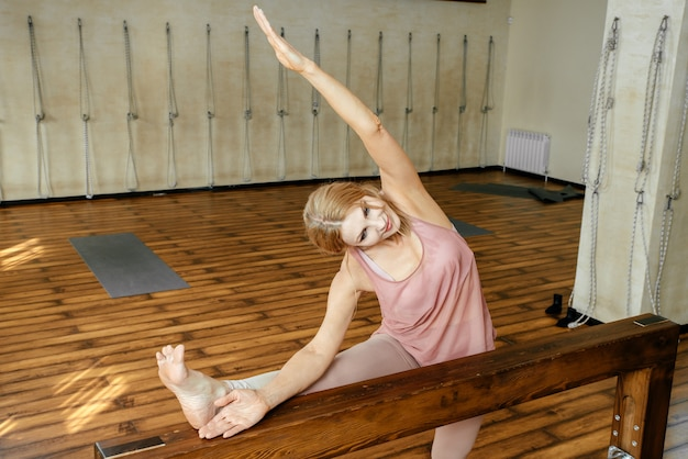 Donna di mezza età che allunga le gambe sulla trave di legno in palestra prima dell'esercizio di yoga