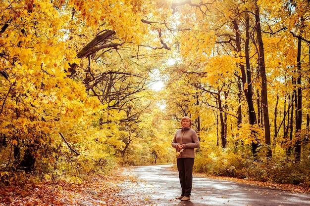 Donna di mezza età circondata da alberi gialli cammina nella foresta autunnale. felice signora anziana che si gode la natura