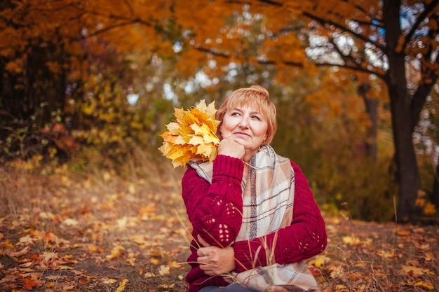 La donna di mezza età circondata da alberi gialli si rilassa nella foresta autunnale. signora che si gode la natura con in mano un mazzo di foglie