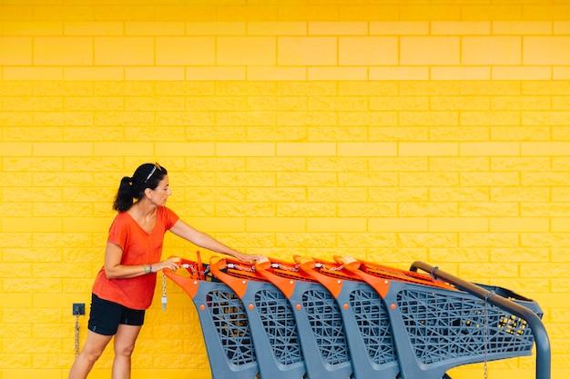 Donna di mezza età che prende un carrello della spesa al supermercato su uno sfondo giallo