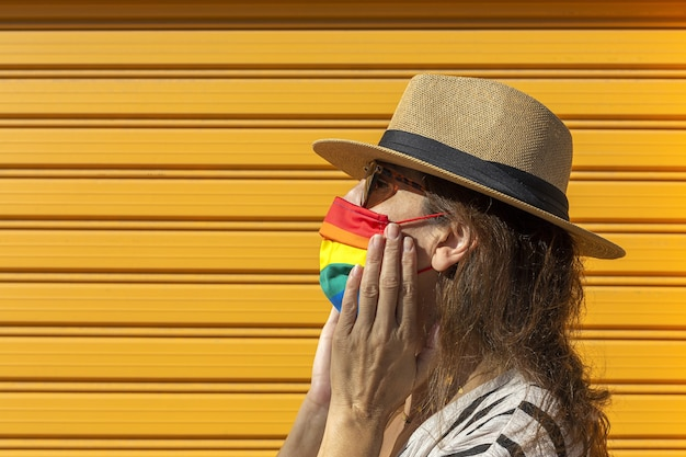 Donna di mezza età che indossa un cappello, occhiali da sole e una maschera protettiva color arcobaleno. lgtb su sfondo giallo. concetto covid-19