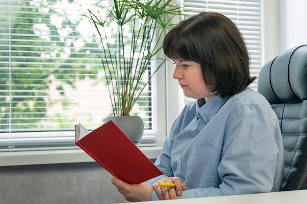 Donna di mezza età durante la lettura del libro. ritratto di donna in poltrona in pelle con libro in mano.
