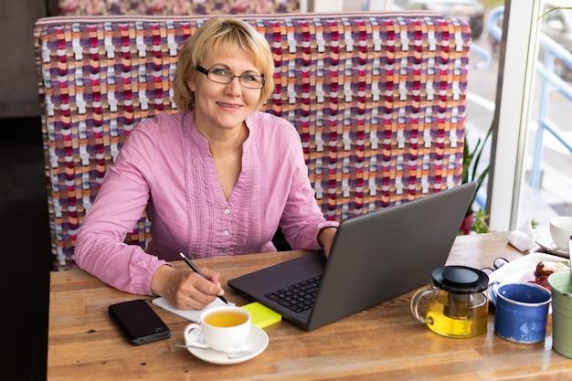 Una donna di mezza età con un laptop lavora in un bar in ufficio, è una libera professionista. donna con gli occhiali seduta al tavolo con una tazza di tisana. è di buon umore.