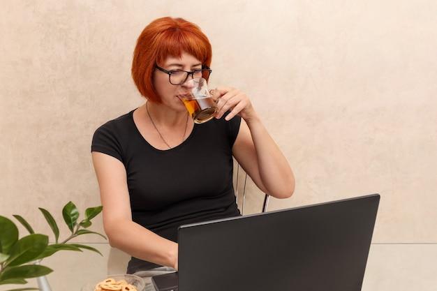 Una donna di mezza età lavora su un laptop da casa e beve il tè