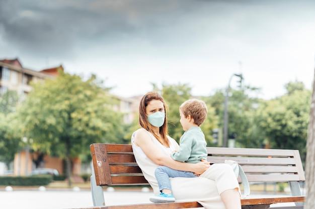 Giovane donna di mezza età con suo figlio seduto su una panchina nel parco con maschera facciale