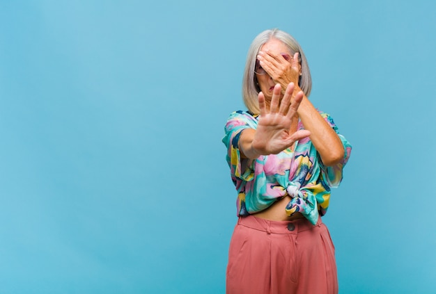 Donna fredda di mezza età che copre il viso con la mano e mette l'altra mano davanti per fermarsi davanti, rifiutando foto o immagini