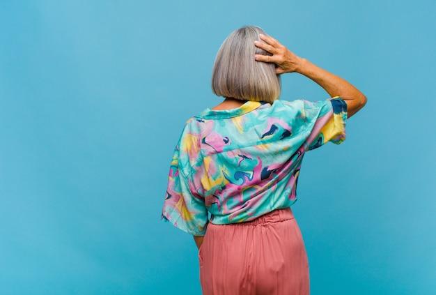 Donna fredda di mezza età che si sente incapace e confusa, pensando a una soluzione, con una mano sul fianco e l'altra sulla testa, vista posteriore