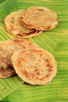 Medio oriente canai o paratha flat bread, o anche conosciuto come roti maryam in indonesia. isolato su sfondo foglia di banana