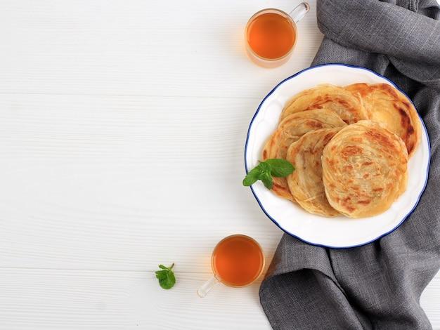 Medio oriente canai o paratha flat bread, o anche conosciuto come roti maryam in indonesia. popolare per la colazione tajil. isolato su sfondo bianco con copia spazio per il testo
