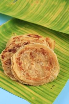 Medio oriente canai o paratha flat bread, o anche conosciuto come roti maryam in indonesia. servito su foglia di banana con copia spazio per il testo