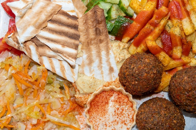 Cucina mediorientale o araba. primo piano di falafel, hummus, tabbouleh, pane pita e verdure, vista dall'alto. tacos vegani. cibo sano vegetariano.