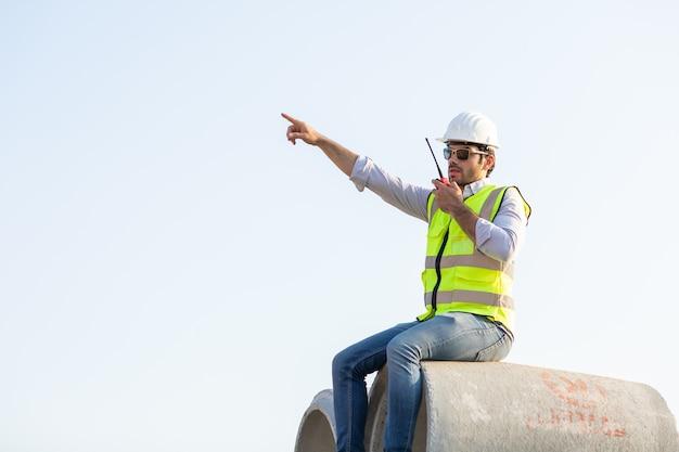 L'ingegnere civile mediorientale fa funzionare il lavoratore alla radio per controllare il lavoro in cantiere.