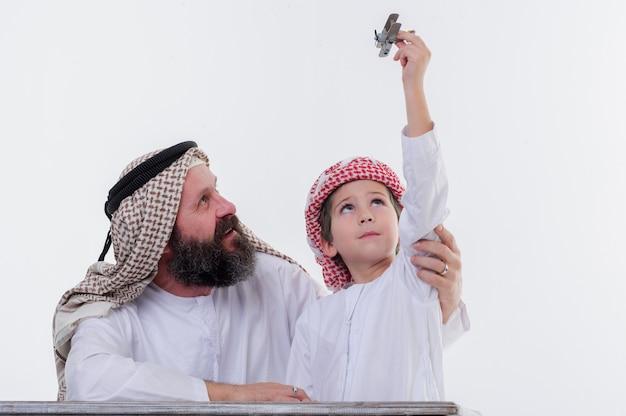 Padre e figlio mediorientali che giocano con l'aereo giocattolo