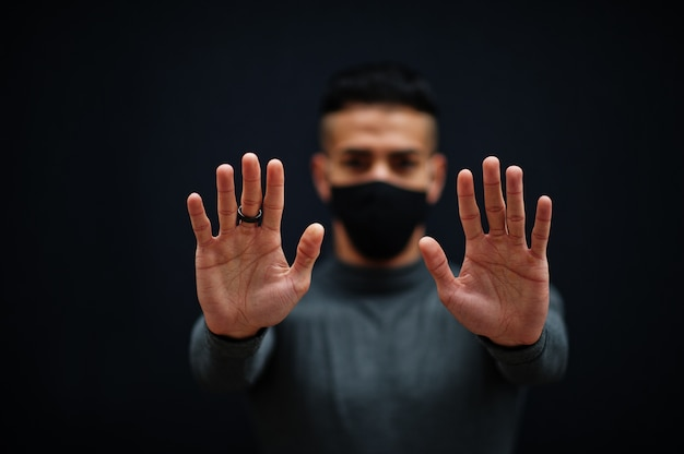 Uomo mediorientale in dolcevita grigio e maschera nera per la protezione del viso