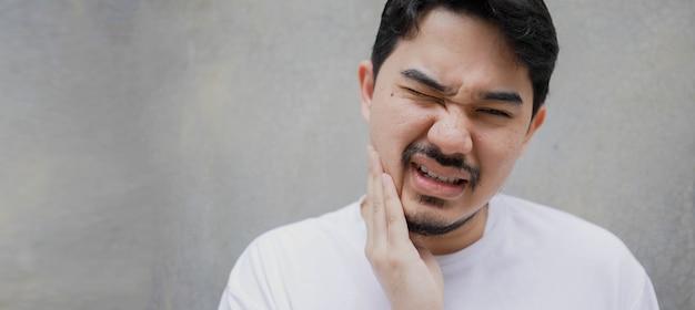 Uomo mediorientale che usa la mano per massaggiare la guancia a causa del dente del giudizio mal di denti