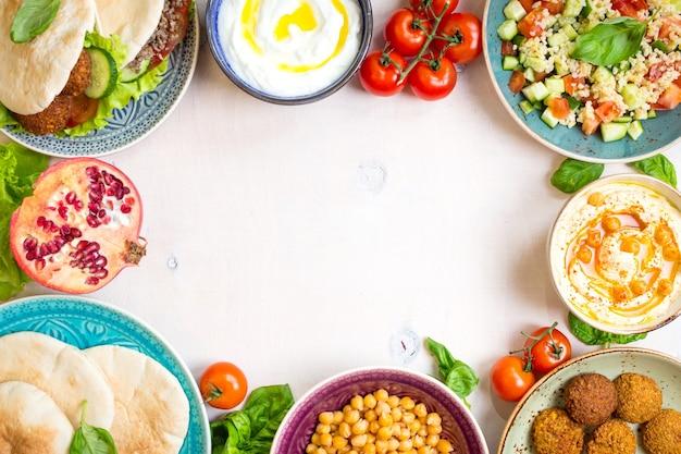 Piatti tradizionali mediorientali su sfondo bianco. doner kebap, pita, ciotola di hummus, falafel
