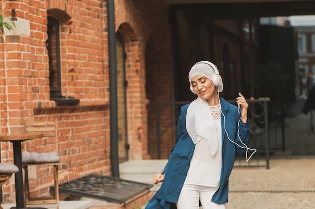 Donna mediorientale in hijab che ascolta musica con le cuffie e balla all'aperto donna