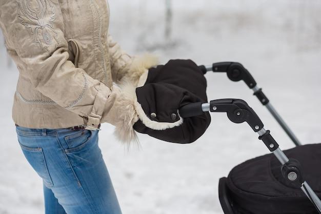 Donna mediorientale con aggancio per passeggino che va a fare una passeggiata in un parco durante un bel pomeriggio invernale