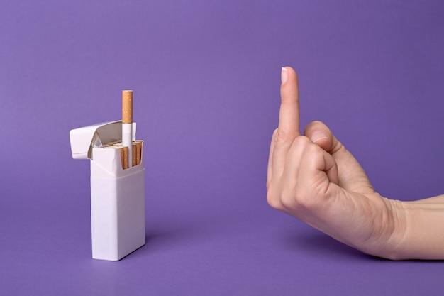 Il dito medio, gesto della mano per un trattamento di sigaretta da un pacchetto, rifiutando la sigaretta.