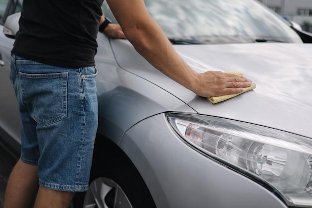 La selezione centrale di un bell'uomo pulisce un'auto con uno straccio in uno showroom in un autolavaggio self-service grigio