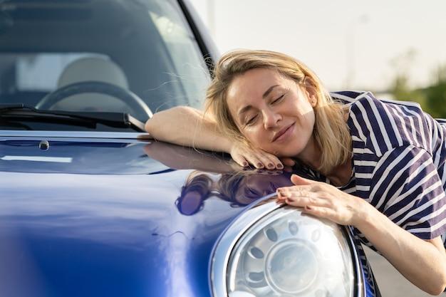 Autista di mezza donna che abbraccia il cofano dell'auto dopo aver dettagliato la lucidatura della pubblicità dell'assicurazione auto