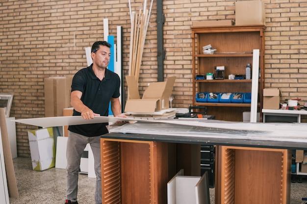 Uomo di mezza età che lavora in un laboratorio di costruzione di mobili