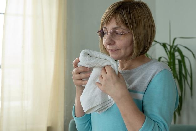 Una donna di mezza età con gli occhiali annusa un asciugamano fresco a casa