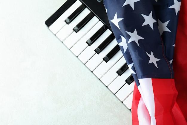 Tastiera midi e bandiera americana su sfondo bianco strutturato