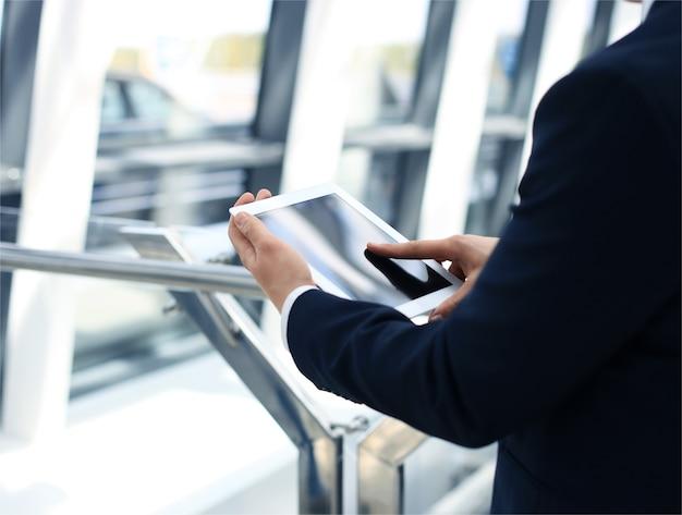 Sezione mediana dell'uomo d'affari con tavoletta digitale in ufficio