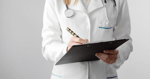 Sezione mediana del medico femminile che tiene appunti e penna compilando documento medico, isolato su bianco